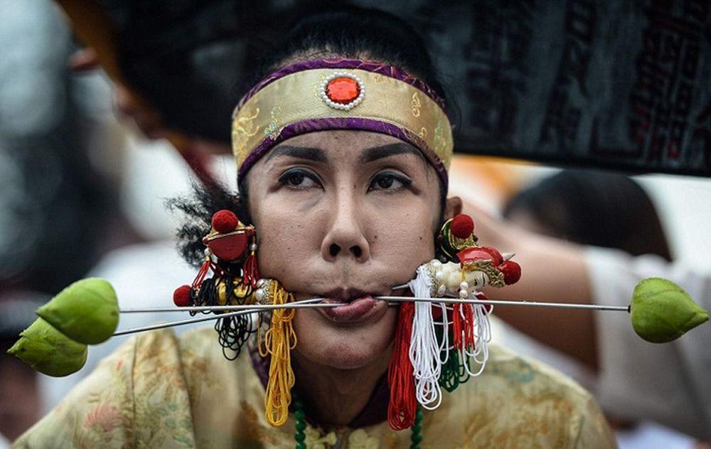 تصاویر : از سوراخ کردن بدن تا راه رفتن بر روی آتش در جشنواره گیاهخواران تایلند